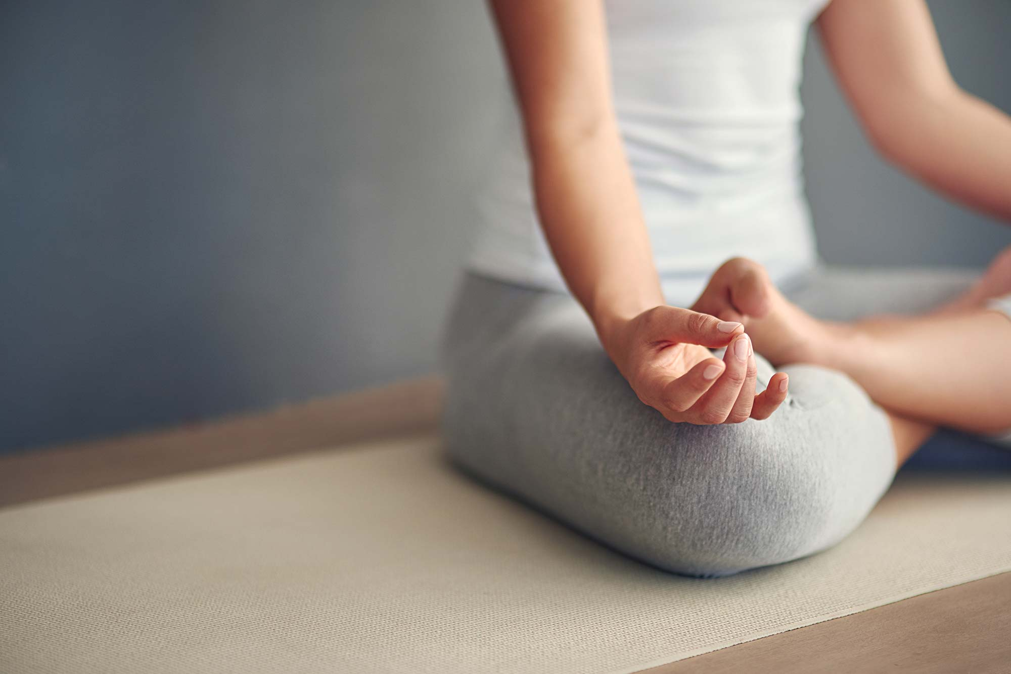 Frau sitzt im Lotus am Boden