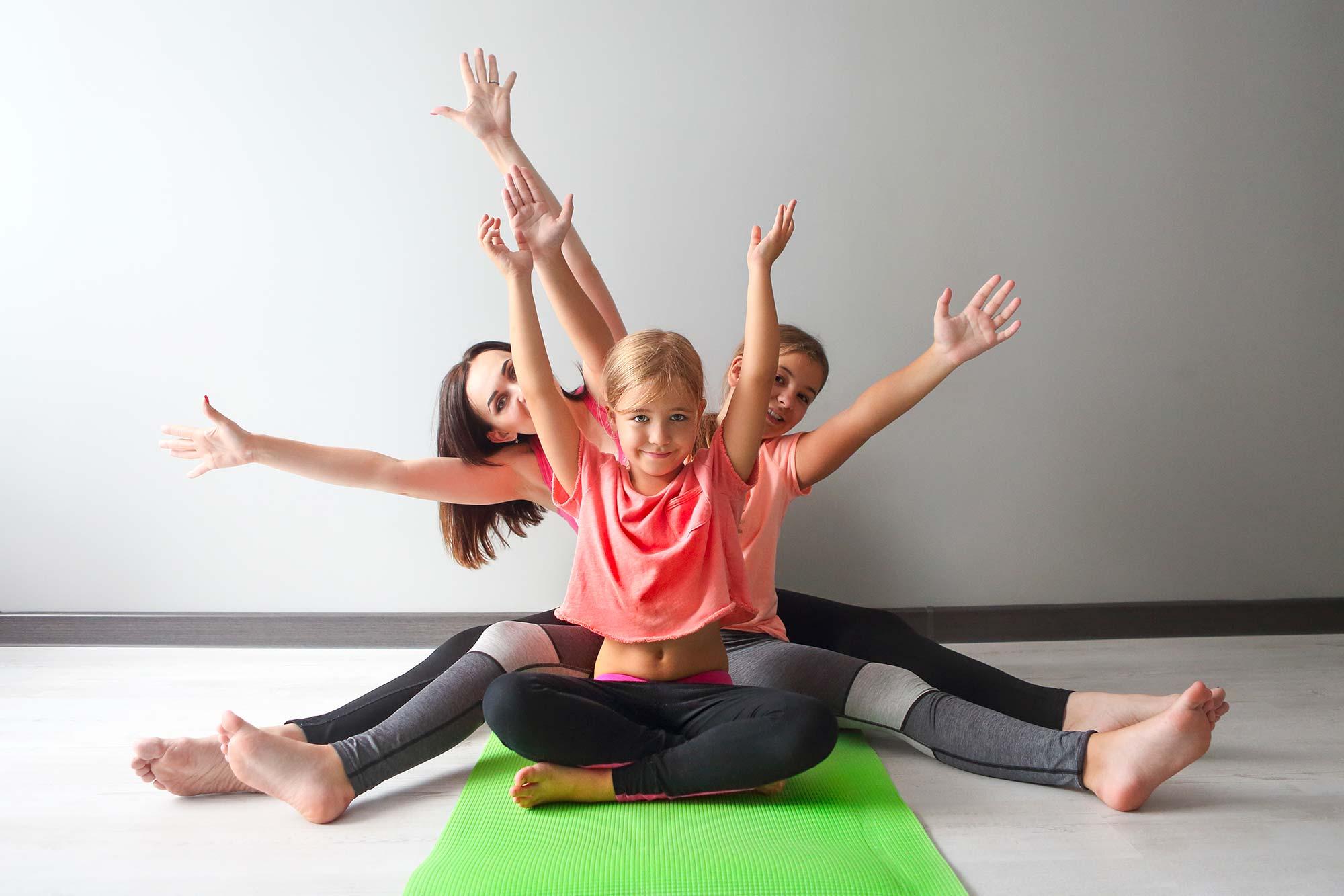 Kinder sitzen in Yogastellung auf Matte