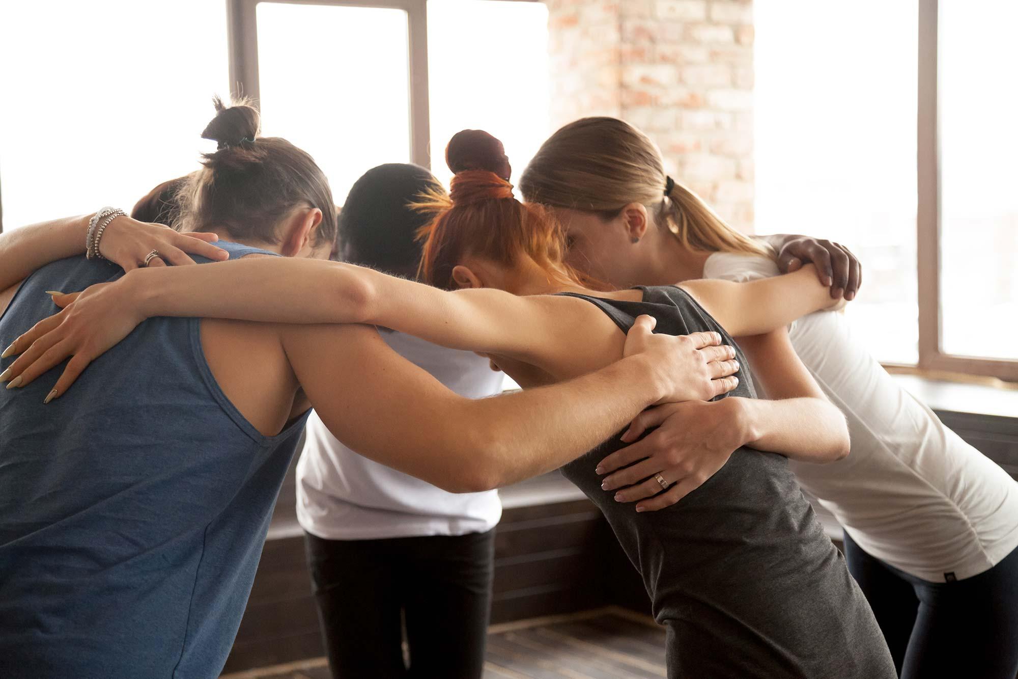 Gruppe von jungen Frauen, im Kreis stehend, einander umarmend, Gemeinschaft